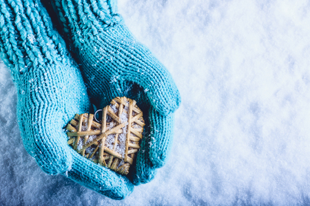st valentine day: Female hands in light teal knitted mittens with entwined beige flaxen heart on a white snow winter background. Love and St. Valentines Day cozy concept. Stock Photo