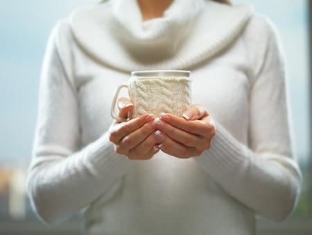 navidad elegante: La mujer sostiene una taza de invierno de cerca sobre fondo claro. Manos de mujer con elegantes uñas manicura francesa diseñar la celebración de una acogedora taza de punto. Invierno y el concepto de la época de Navidad.