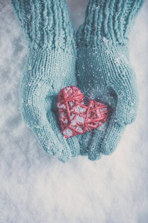 hands holding heart: Woman hands in light teal knitted mittens are holding a beautiful glossy red heart in a snow winter background. Love and St. Valentine concept. Stock Photo