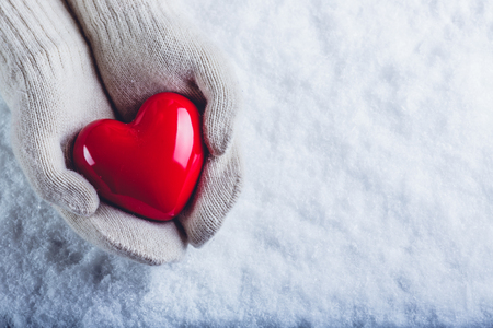 white winter: Female hands in white knitted mittens with a glossy red heart on a snow winter background. Love and St. Valentine cozy concept.