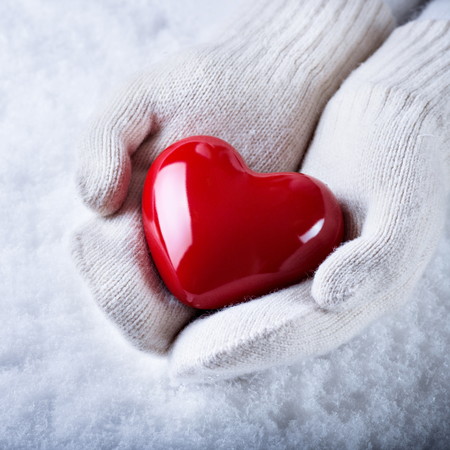 st  valentine: Female hands in white knitted mittens with a glossy red heart on a snow background.  Love and St. Valentine concept.
