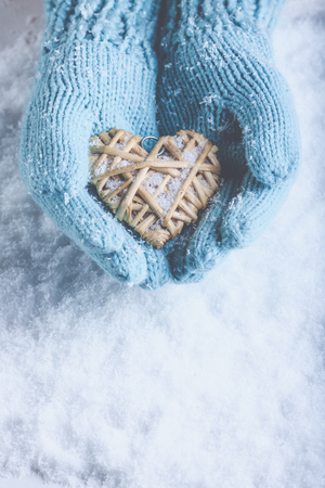 flaxen: Female hands in light teal knitted mittens with entwined beige flaxen heart on a white snow winter background. Love and St. Valentines Day cozy concept. Stock Photo