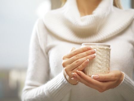 christmas manicure: Woman holds a winter cup close up. Woman hands with elegant french manicure nails design holding a cozy knitted mug. Winter and Christmas time concept.