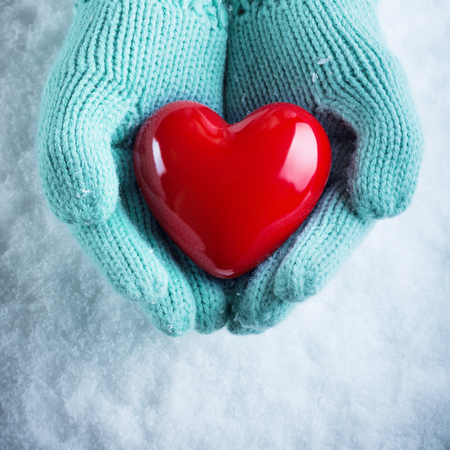st  valentine: Woman hands in light teal knitted mittens are holding a beautiful glossy red heart in a snow background. Love and St. Valentine concept. Stock Photo