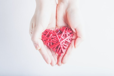 entwined: Female hands with a entwined vintage romantic red heart on a snow background. Love and St. Valentine concept.