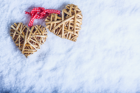 flaxen: Two beautiful romantic vintage entwined beige flaxen hearts tied together with a ribbon on a white snow winter background. Love and St. Valentines Day concept.