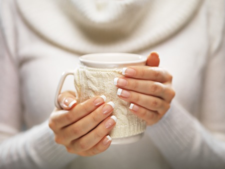 christmas manicure: Woman holds a winter cup close up on light background. Woman hands with elegant french manicure nails design holding a cozy knitted mug. Winter and Christmas time concept.