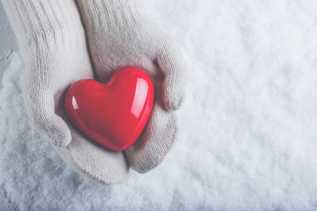human's arm: Female hands in white knitted mittens with a glossy red heart on a snow winter background. Love and St. Valentine cozy concept.
