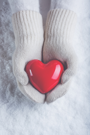 women  s fashion: Female hands in white knitted mittens with a glossy red heart on a snow winter background. Love and St. Valentine cozy concept.