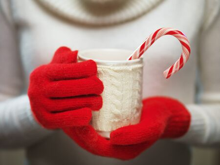 chocolate candy: Woman holds a winter cup close up. Woman hands in woolen red gloves holding a cozy mug with hot cocoa, tea or coffee and a candy cane. Winter and Christmas time concept.