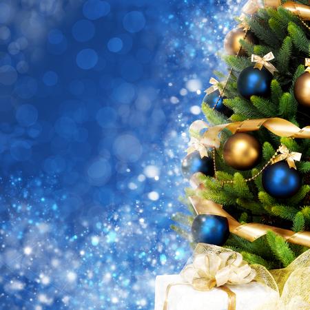 moños navideños: Mágicamente decorado árbol de Navidad con bolas, cintas y guirnaldas en una borrosa azul brillante, hadas y fondo espumoso;