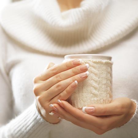 manicura: La mujer sostiene una taza de invierno de cerca sobre fondo claro. Manos de mujer con elegantes uñas manicura francesa diseñar la celebración de una acogedora taza de punto. Invierno y el concepto de la época de Navidad.
