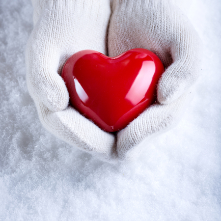 s day: Female hands in white knitted mittens with a glossy red heart on a snow winter background. Love and St. Valentine cozy concept.
