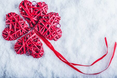red clover: beautiful romantic vintage red hearts together in clover shape on a white snow background. Love and St. Valentines Day concept. Stock Photo