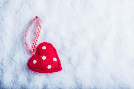 Red toy suave heart on a frosty white snow winter background. Love and St. Valentine concept. Фото со стока