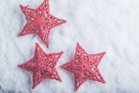 Three Beautiful magical vintage red stars on a white snow background. Winter and Christmas concept. Фото со стока