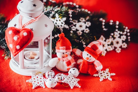 Cute couple of little adorable snowmen is standing near the white fairy lantern with a toy heart on it and decorated fir tree branch behind it. Christmas card with copy space for your text. Фото со стока