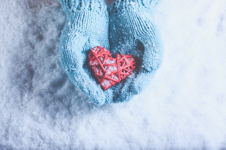 Woman hands in light teal knitted mittens are holding a beautiful a entwined vintage romantic red heart in a snow background. Love and St. Valentine concept. Фото со стока