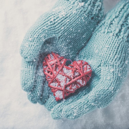 Woman hands in light teal knitted mittens are holding a beautiful glossy red heart in a snow winter background. Love and St. Valentine concept. Фото со стока