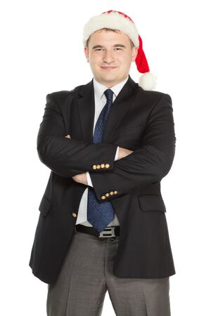 Cheerful businessman wearing a Santas' hat is standing isolated on a white background