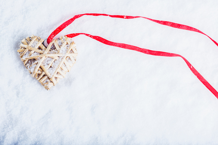 Beautiful magical vintage beige heart tied with a red ribbon on a white snow background. Winter and Christmas concept.