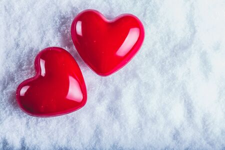 Two red glossy hearts on a frosty white snow winter background. Love and St. Valentine concept. Фото со стока