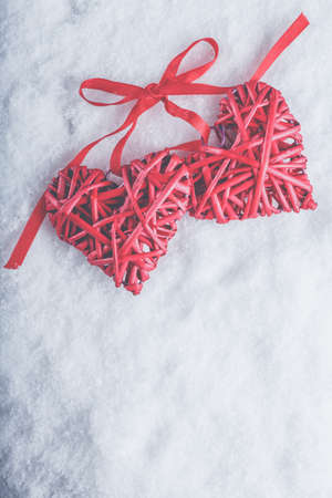Two beautiful romantic vintage red hearts tied together with a ribbon on a white snow winter background. Love and St. Valentines Day concept. Фото со стока