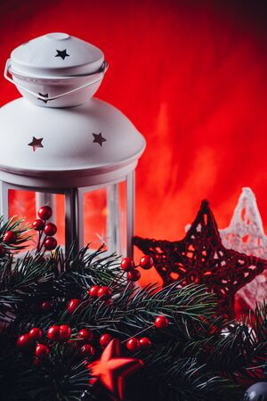 Christmas white lantern is standing with a burning candle in it with a fir tree branch and knit stars in front of it on a red background. Christmas fairy tale card with copy space for your text. Фото со стока