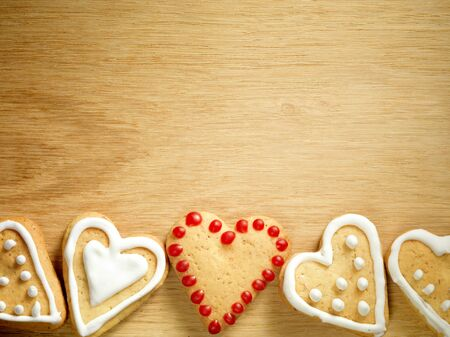Gingerbread cookies hanging over wooden background, Christmas and Valentine's Day concept.