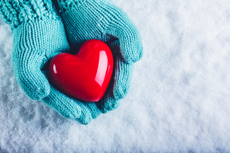 Woman hands in light teal knitted mittens are holding a beautiful glossy red heart in a snow winter background. Love and St. Valentine cozy concept. Фото со стока