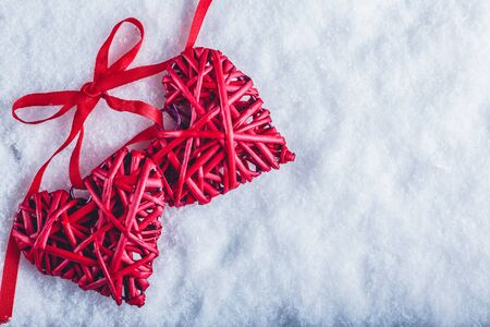 tied together: Two beautiful romantic vintage red hearts tied together with a ribbon on a white snow winter background. Stock Photo