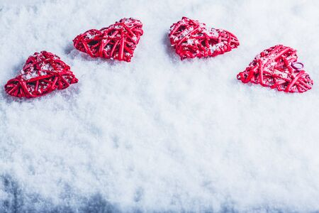 Four red hearts on a white snow winter background. Stock Photo