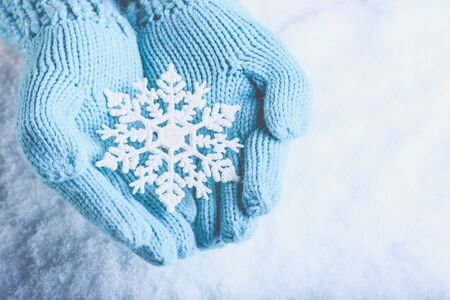 Female hands in light teal knitted mittens with snowflake on snow background. Stock Photo