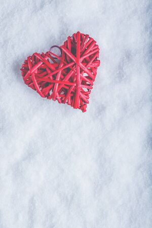 A red heart on a white snow winter background.