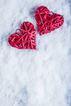 Two red hearts on a white snow winter background. Stock Photo
