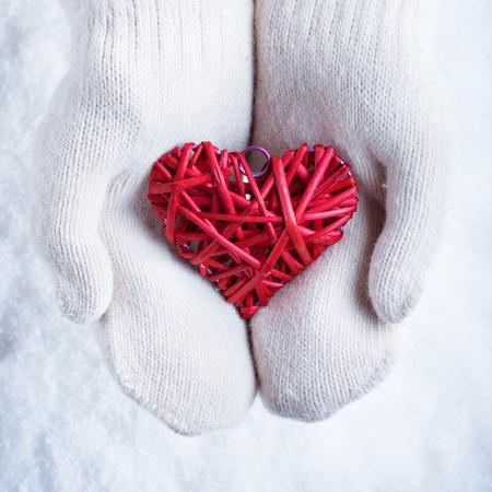 Ženské ruce v bílých pletených rukavic s propletené vintage romantické červené srdce na pozadí sněhu.