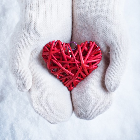 st  valentines day: Female hands in white knitted mittens with a entwined vintage romantic red heart on a snow background.