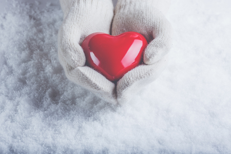human's arm: Female hands in white knitted mittens with a glossy red heart on a snow winter background. Stock Photo