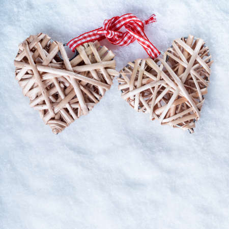 entwined: Two beautiful romantic vintage entwined beige flaxen hearts tied together with a ribbon on a white snow winter background.