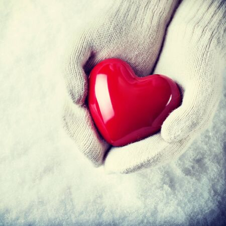 heart in hand: Female hands in white knitted mittens with a glossy red heart on a snow background. Stock Photo