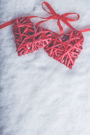 Two red hearts tied together on a white snow winter background.