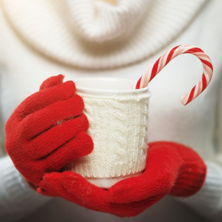 Woman hands in woolen red gloves holding a cozy mug with hot cocoa, tea or coffee and a candy cane. Stock Photo