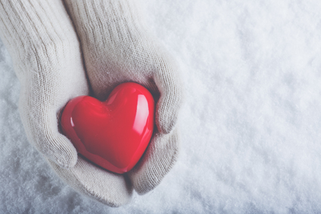 s day: Female hands in white knitted mittens with a glossy red heart on a snow winter background. Stock Photo