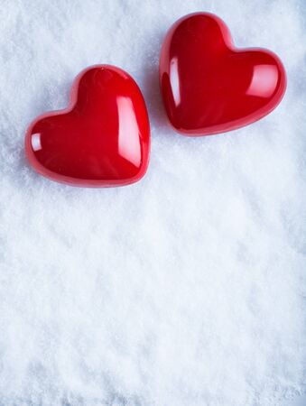 Two glossy red hearts on a white snow winter background.