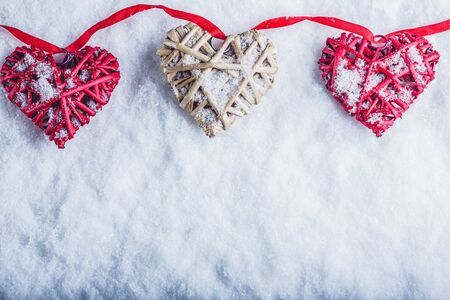Three vintage hearts are hanging on a red band on a white snow winter background.