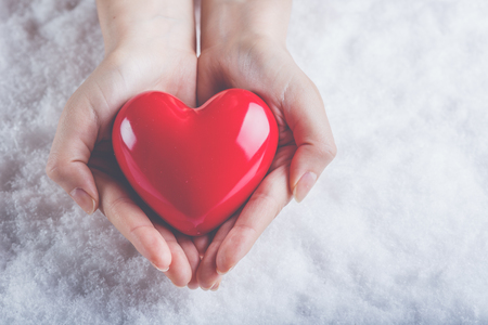 heart hands: Woman hands are holding a beautiful glossy red heart in a snow winter background. Stock Photo