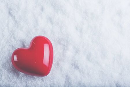 A glossy red heart on a white snow winter background.