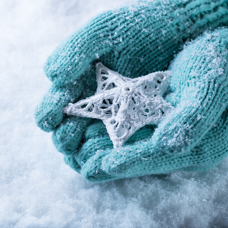 human's arm: Female hands in light teal knitted mittens with entwined white star on a white snow background.