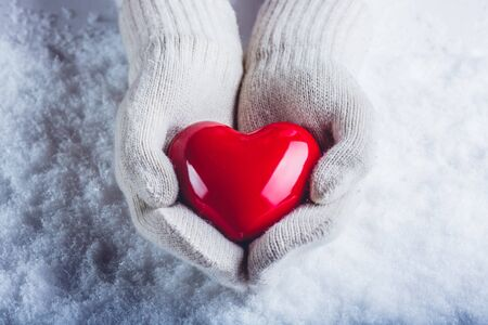 Female hands in white knitted mittens with a glossy red heart on snow