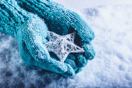 human's arm: Female hands in light teal knitted mittens with entwined white star on a white snow background. Winter and Christmas cozy concept.